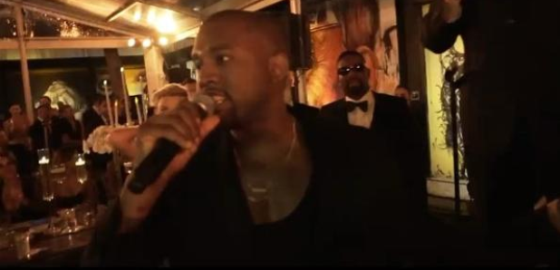 Kanye West holding microphone